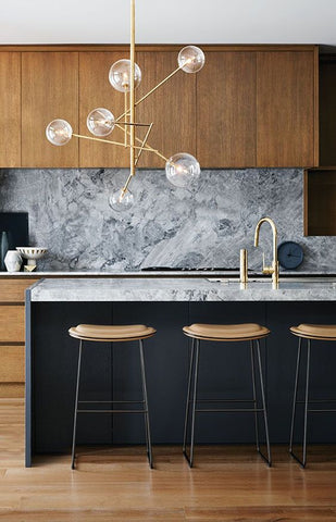 Statement lighting fixtures create a mesmerising, modern twist to any kitchen island, plus much more. It breaks away the regular, symmetrical décor, thanks to the clusters of lights