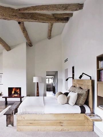 The exposed wooden beams in this wonderfully white bedroom add a modern rustic touch to the decor.