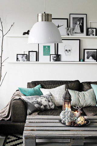 This Scandinavian inspired living room speaks subtly industrial. The industrial light and scavenged wood table brings out a raw character amongst the black and aqua inspired home decor.