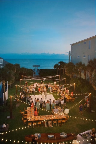 This beachside reception is gorgeously dominated by the ambient glow of the festoon lights that hung overhead with a quaint, criss-cross pattern.