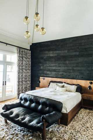This rather moody looking bedroom makes use of an interesting drop chandelier and two kohl-coloured wall lamps