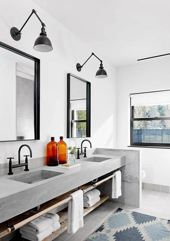 Balance is beautiful. Two wall lamps installed atop two mirrors create a perfect, symmetric look. This design creates clean, orderly character in the muted-toned bathroom