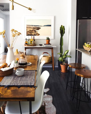 White walls and a black floor, and a hint of glossy bronze textures put the modern in this rustic dining setting. Pendant light over dining table to finish of the look