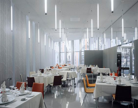 Who says linear lighting is limited to horizontal use An interior design firm created a dazzling light work by vertically hanging linear light tubes