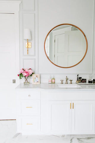 a chic marble slab sink accentuated with bright brass faucets, wall lamps and mirrors