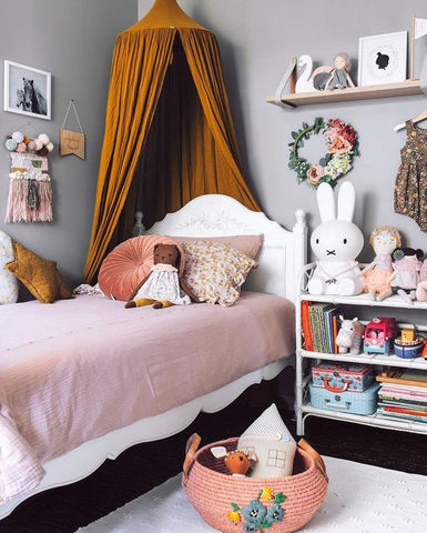a tranquil pastel-coloured room where greys and browns mix, brightened up with a splash of blood orange. Little wall decor like flower crowns, buntings and tassels, add to the spectacle