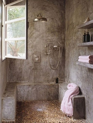 industrial bathroom, raw concrete is used as a canvass for a minimalist, quiet shower area