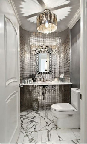 what a powder room! Go extravagant by going eclectic--this design makes use of rich, textured tiles, marble flooring and jeweled tones highlighted with over the top mirror and flush mount ceiling light.