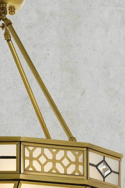 Balanced angular antique brass suspension rods atop art deco shade with crystal and geometric design