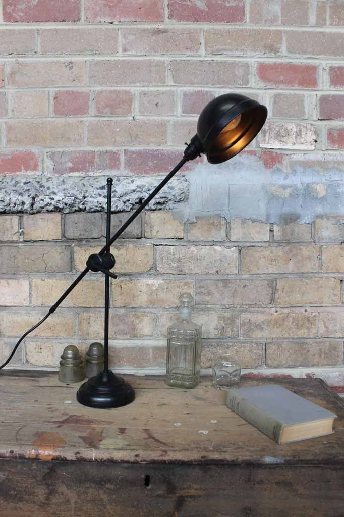 French industrial brass desk lamp has an adjustable boom arm tilting the lamp shade up or down to the desired angle