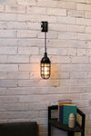 Hanging wall light bunker cage over side table used as task lighting