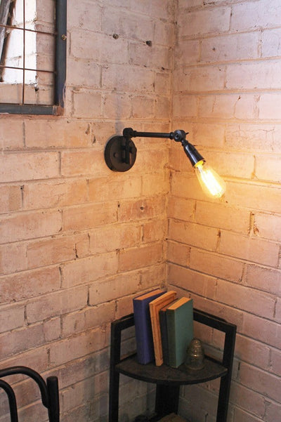 Industrial swing arm wall light with teardrop edison bulb.