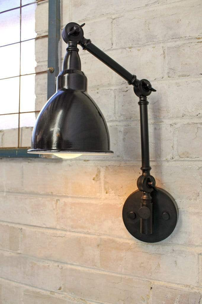 Industrial two arm swing wall lamp with black enamel shade and large round edison bulb