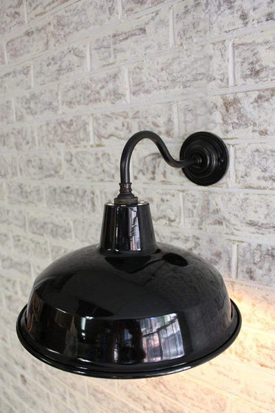 Industrial warehouse gooseneck wall light on bare brick wall