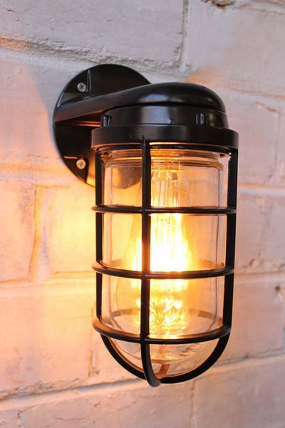 Industrial ocean liner wall light on exposed brick wall