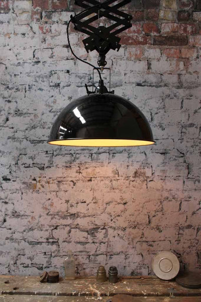 Large industrial scissor light. robust. black pendant light. a smooth glossy black outer finish and contrasting white inner. online lighting.
