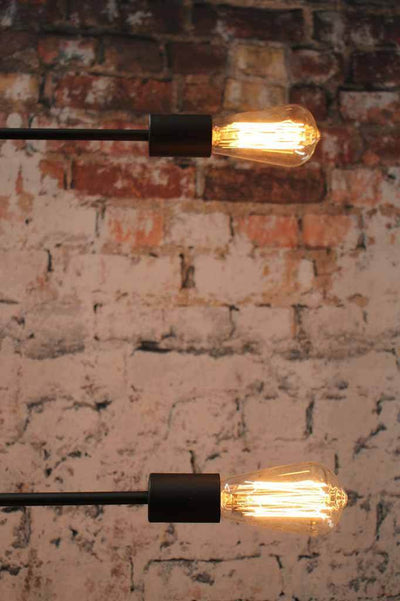 Modern industrial lighting. Matt black lighting piece with moveable arms. Exposed light bulbs.