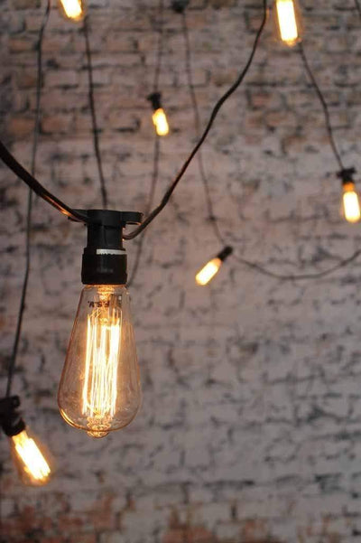 Outdoor festoon string lights with edison light bulb squirrel cage filament. old school bulbs