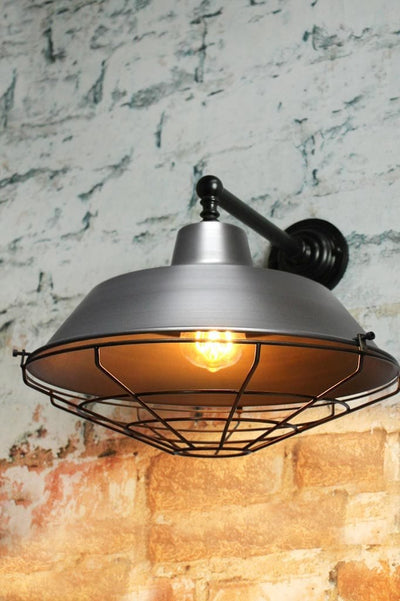 Raw steel wall light with antique brass cage guard