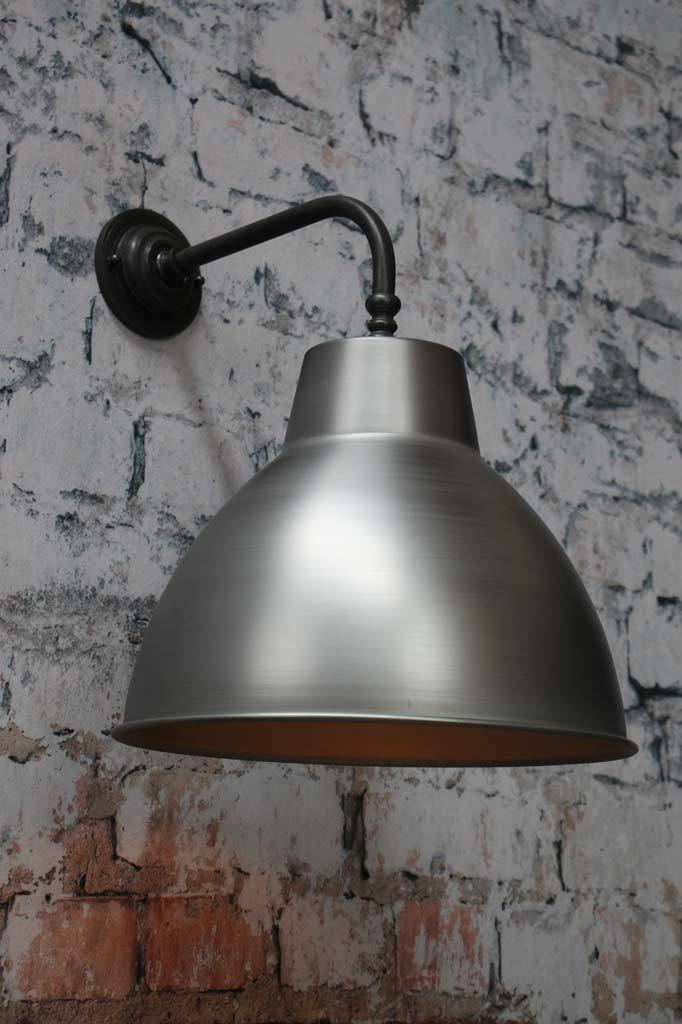 Raw steel wall light with brass arm
