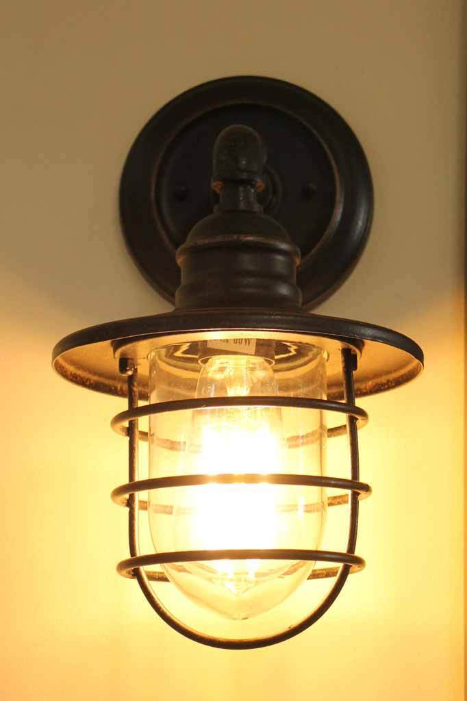 Shorehouse outdoor wall light. glass shade with cage outer