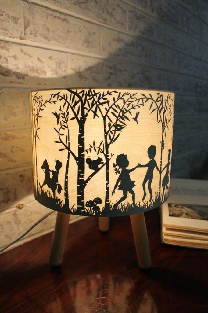 Timber table lamp with children playing in the woods