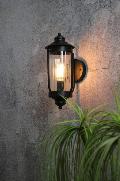 Black outdoor wall light with clear glass shade.