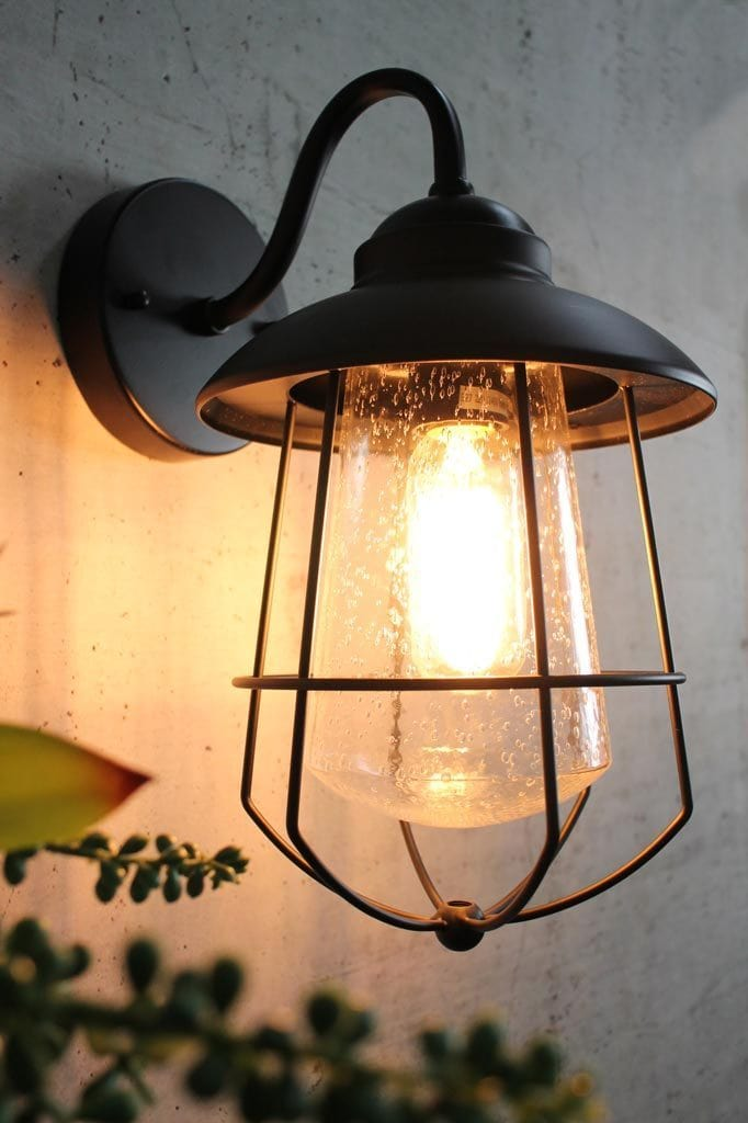 Black steel outdoor porch light with droplet glass shade and wire cage