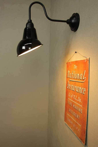 Black shade is angled to illuminate a wall or object such as a menu sign or artwork.