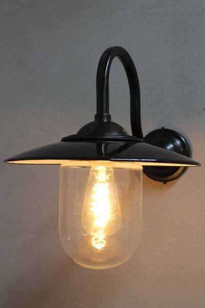 Boathouse glass wall light has a protective glass shade to house its edison filament led light bulb and sits on a black gooseneck wall sconce.