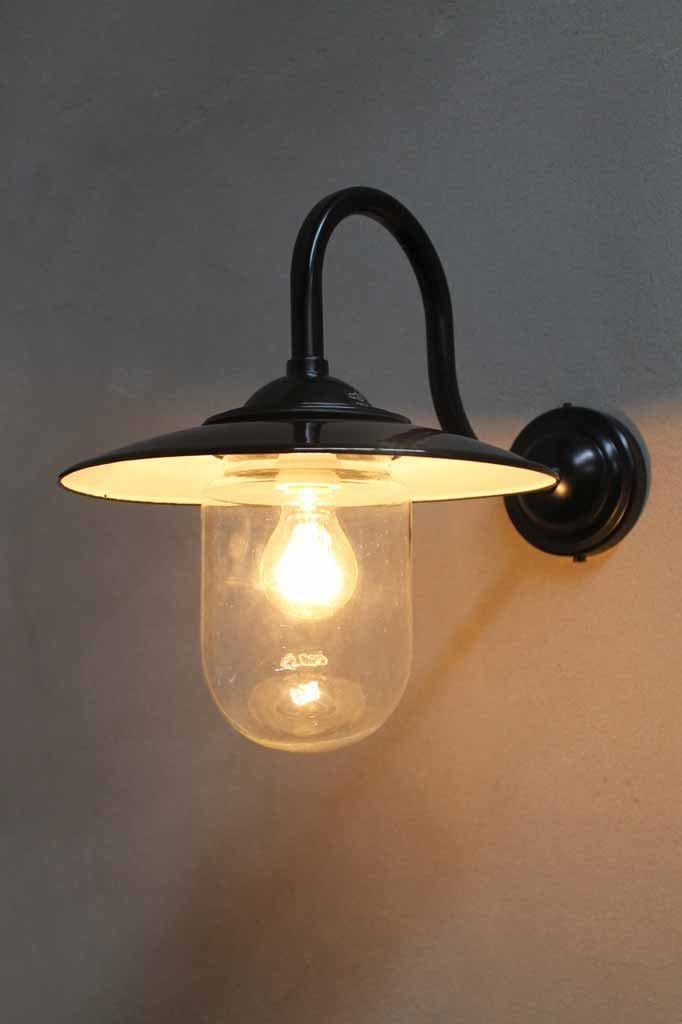 Boathouse glass wall light has a protective glass shade to house its edsion light bulb and sits on a black gooseneck wall sconce. glossy black shade with white inner holds the bulb