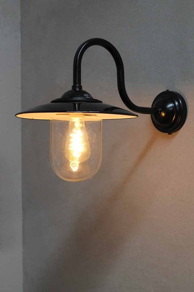 Boathouse glass wall light has a protective glass shade to house its light bulb and sits on a black gooseneck wall sconce.