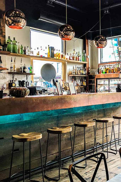 Copper pendant lights over bar