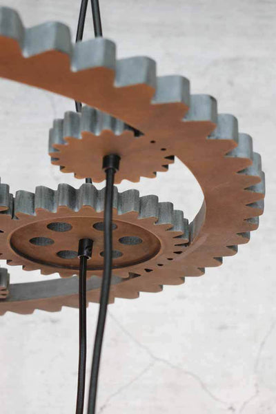 hanging light consists of a round carved wooden fixture in the shape of machinery gears