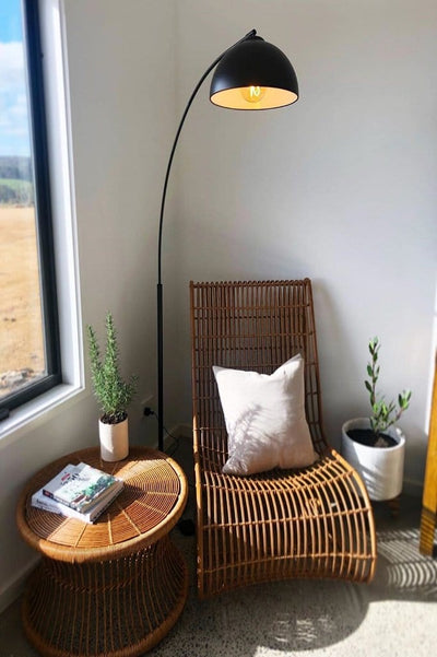 scandinavian arc floor lamp atop armchair