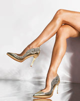"Aubree pumps in Metallic gold calf leather elongates her legs in these pointed toe pumps featuring asymmetrical Swarovski crystal hummingbird ornament, natural leather welt and gold mirror 4"" or 100mm heel."
