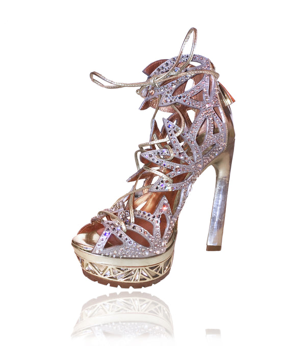 Ciara lace-up gladiator sandals in a laser cut floral pattern in metallic stardust kid suede and 1,700 clear Swarovski crystals on her upper will have you sparkling with every step! They feature a back zipper for easy entry and a metallic gold art deco inspired platform and rubber lugg sole to prevent slips on the go. These are the perfect wedding shoes for the bride to be.