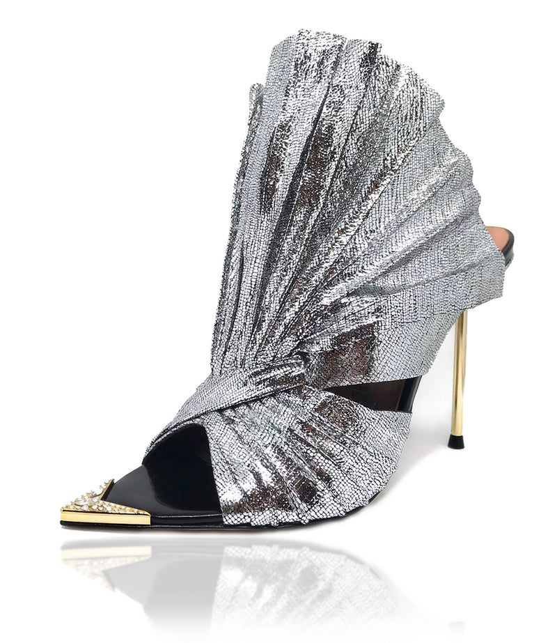 Devon mules in pleated silver metallic lizard effect baby calf leather is sculpted to create a scalloped fan effect. The metal toe rand features inlaid Swarovski crystals that will have her glittering with every step. A rubber pod recessed into the sole helps prevent slipping on the go. There is a 4'' or 100mm gold metal stiletto heel.