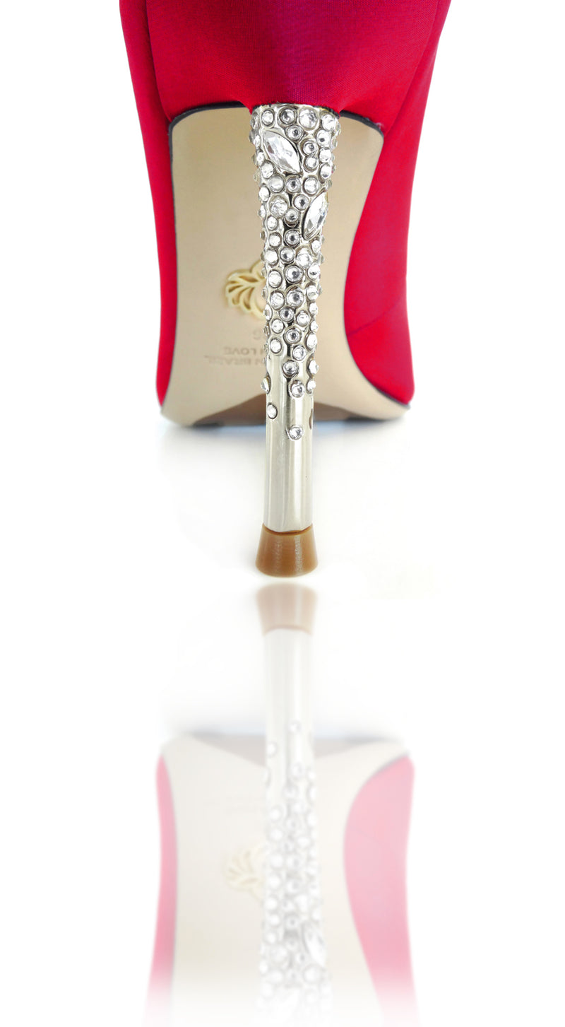 "Nadia is a pointed toe pump with an opulent heel featuring clusters of Swarovski crystals that glitter while you walk. A rubber pod is recessed into the outsole to prevent slips. 4"" or 100mm silver metal heel."
