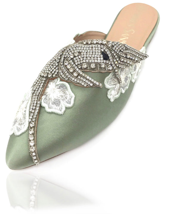 Sadira silk satin mule features an almond toe. Embellished with tiny hand-placed encased Swarovski crystals, the precious hummingbird ornament lays delicately on this silhouette. Surrounded by embroidered flowers adorning the foot as elegant jewelry, you will be glittering like diamonds at dusk. There is also a rubber pod recessed into the sole to help prevent slipping on the go.