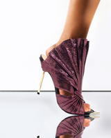 Devon mules in pleated wine metallic lizard effect baby calf leather is sculpted to create a scalloped fan effect. The metal toe rand features inlaid Swarovski crystals that will have her glittering with every step. A rubber pod recessed into the sole helps prevent slipping on the go. There is a 4'' or 100mm gold metal stiletto heel.