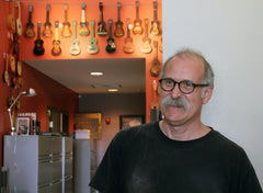 Collings' Bruce Van Wart in front of Collings' vintage uke collection