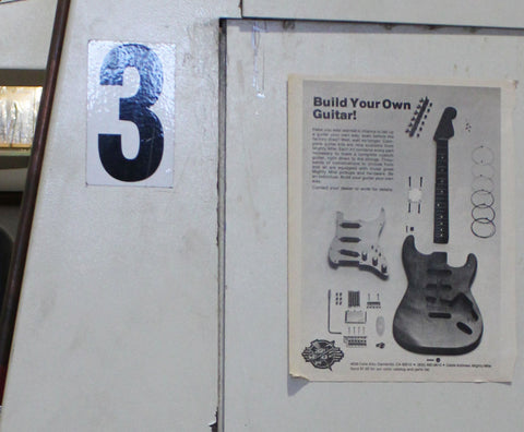 Vintage 'build your own guitar' magazine ad on a machine at the Collings facility