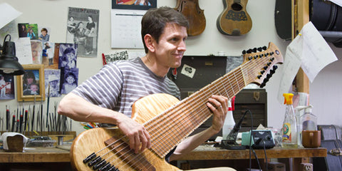 Mike Horan at his bench holding a very, very large bass guitar
