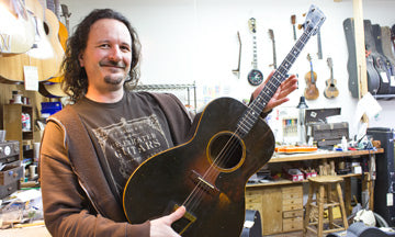 Mike Runyon at his luthiery bench with a recently repaired guitar