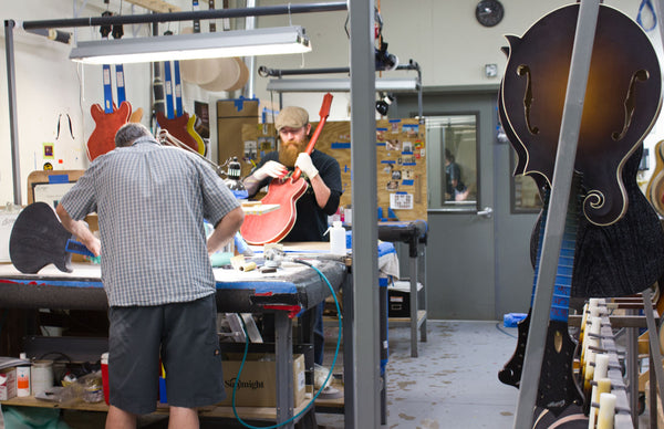 Finish work on some electric guitars at the Collings facility