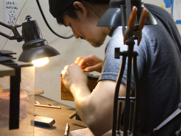 hand work being done at collings guitars making bridges