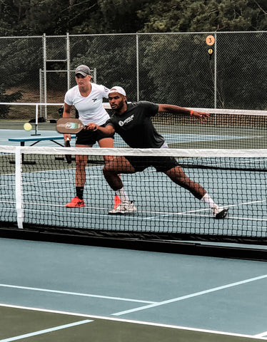 top level pickleball player man reaching for ball to poach from partner