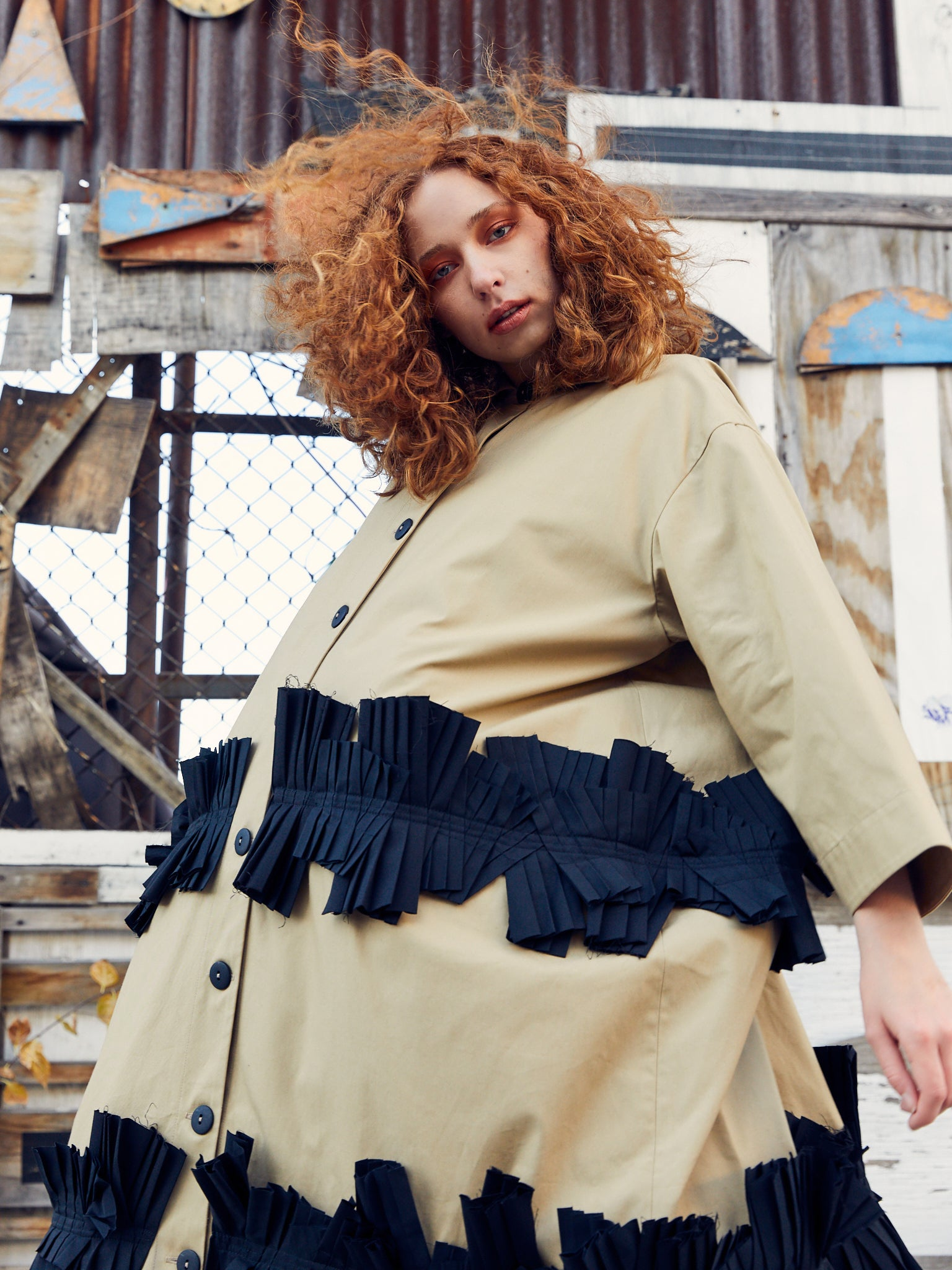 Tan long jacket with two rows of black attached pleating details by Nancy Stella Soto