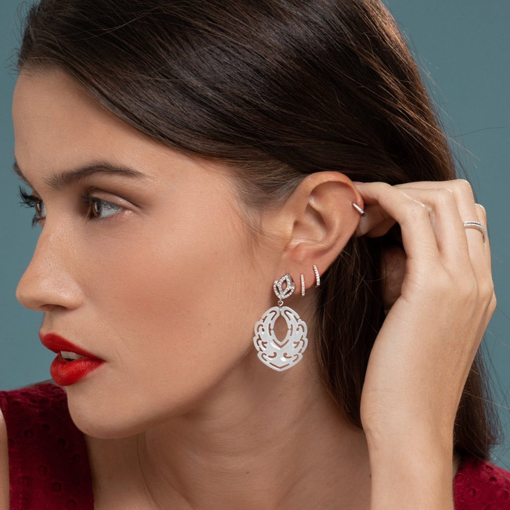 Lilian wearing the Diamond Lotus and White Jade Earrings, White Gold Diamond Huggies Medium and the White Gold Diamond Huggy Small by McFarlane Fine Jewellery